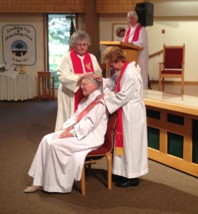 Praying over newly ordained woman priest
